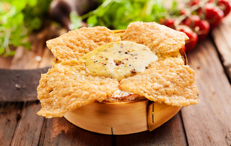 Crispy fried or roasted camembert oven cheese dip. With a soft succulent center served in its original wooden box with fresh salad ingredients behind on a royalty free stock photography
