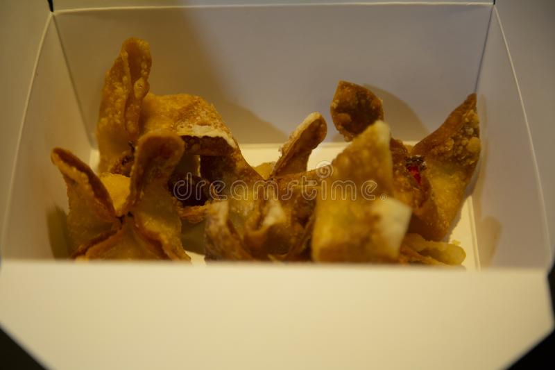 Fried Wontons In Takeout Box. Crispy, fried wontons filled with cream cheese in a takeout box stock photo