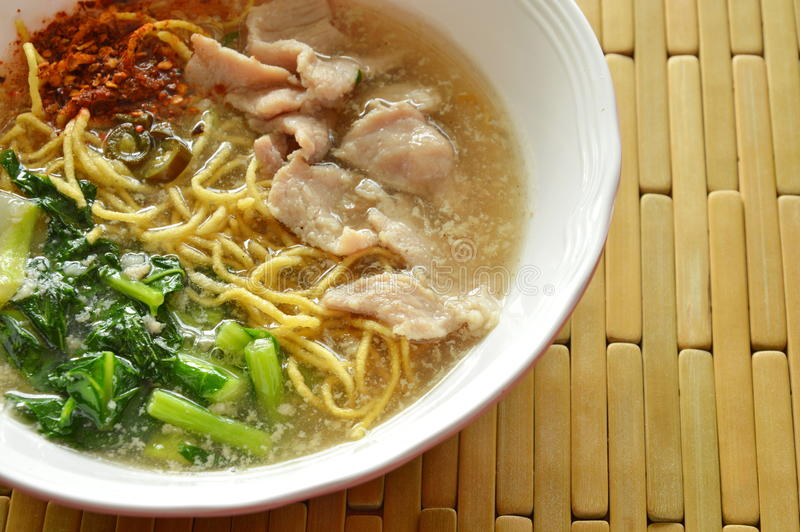 Crispy fried yellow noodle with marinated pork and Chinese kale in gravy sauce. On bowl royalty free stock image