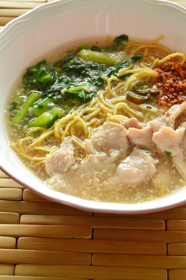Crispy fried yellow noodle with marinated pork and Chinese kale in gravy sauce. On bowl stock images