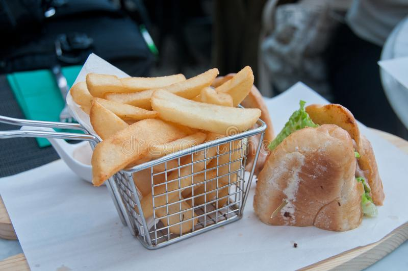 Crispy golden hand cut chips deep fried with French handmade sandwich served on white paper royalty free stock photos