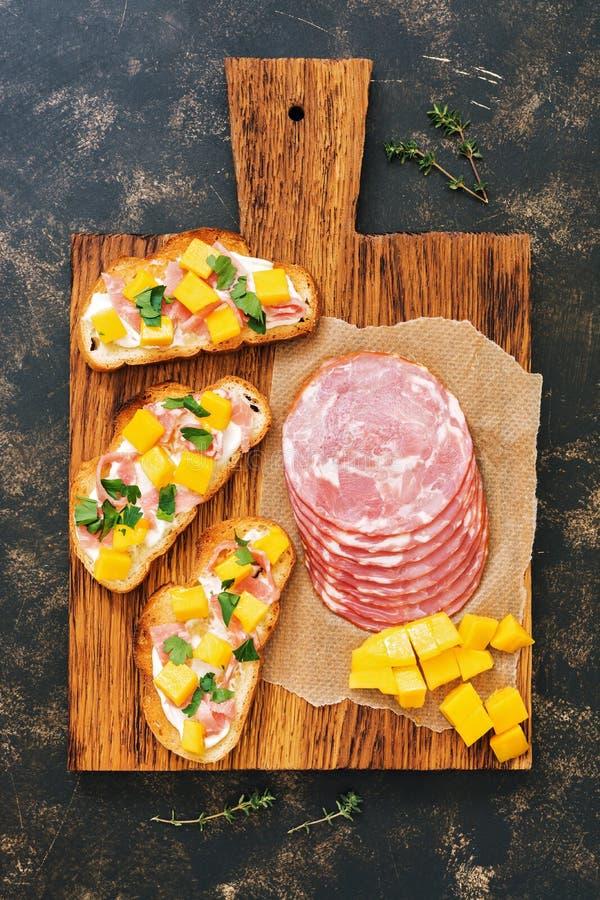 Crispy grzanka z kremowym serem, baleron i mango na drewnianej desce, ciemny tło, odgórny widok fotografia stock