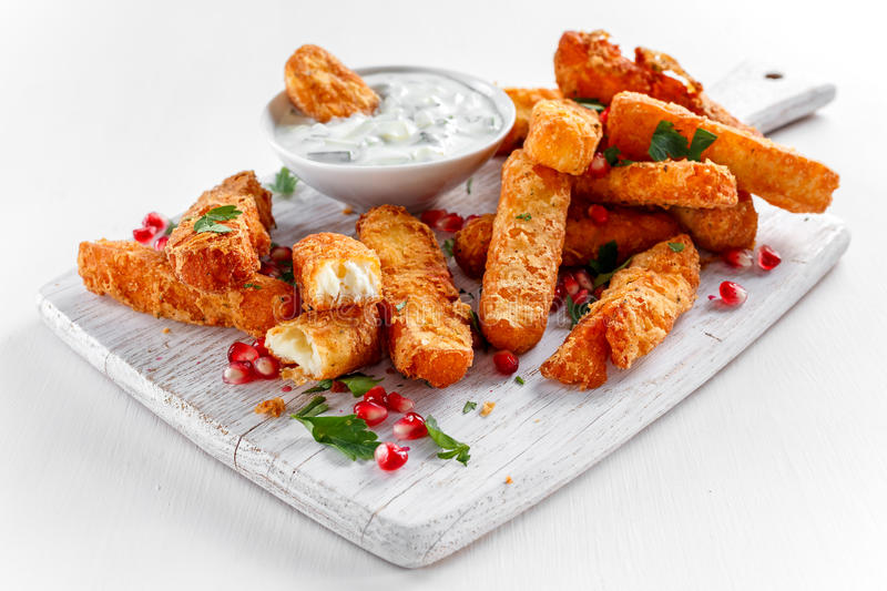 Crispy Halloumi cheese sticks Fries with yogurt for dipping and pomegranate seeds. royalty free stock photography