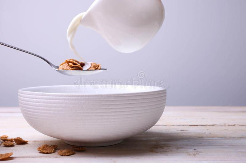 Dry cereal flakes. Crispy healthy dry cereal with milk, pour in deep plate on wooden table on neutral background. Copy space royalty free stock photos