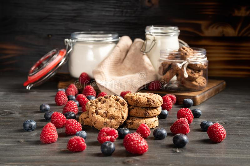 Crispy homemade chocolate biscuits, raspberries and blueberries royalty free stock images