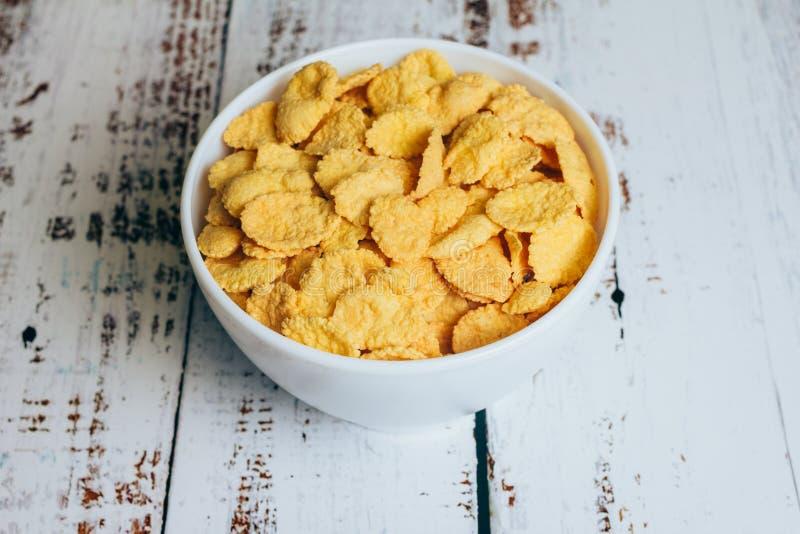 Crispy kukurydzani płatki w pucharze na stole obrazy stock