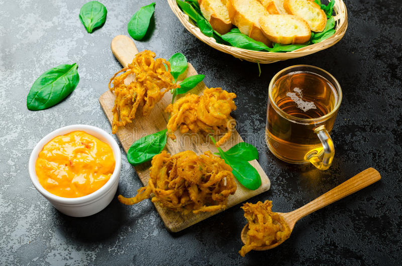 Crispy Onion Bhajis. With creame cheese dip with jalapeno and crunchi toast on spinach leaves and czech beer royalty free stock images