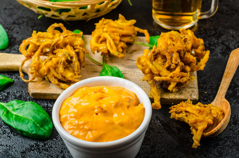 Crispy Onion Bhajis. With creame cheese dip with jalapeno and crunchi toast on spinach leaves and czech beer stock photography