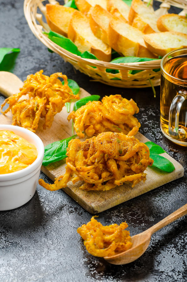 Crispy Onion Bhajis. With creame cheese dip with jalapeno and crunchi toast on spinach leaves and czech beer stock photos