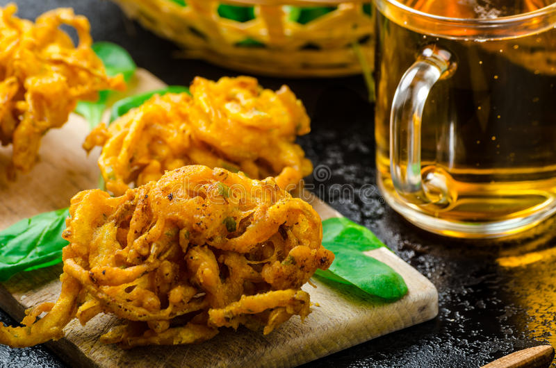 Crispy Onion Bhajis. With creame cheese dip with jalapeno and crunchi toast on spinach leaves and czech beer royalty free stock image