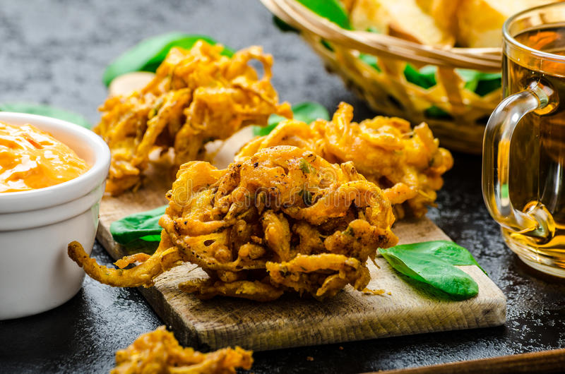 Crispy Onion Bhajis. With creame cheese dip with jalapeno and crunchi toast on spinach leaves and czech beer stock photo