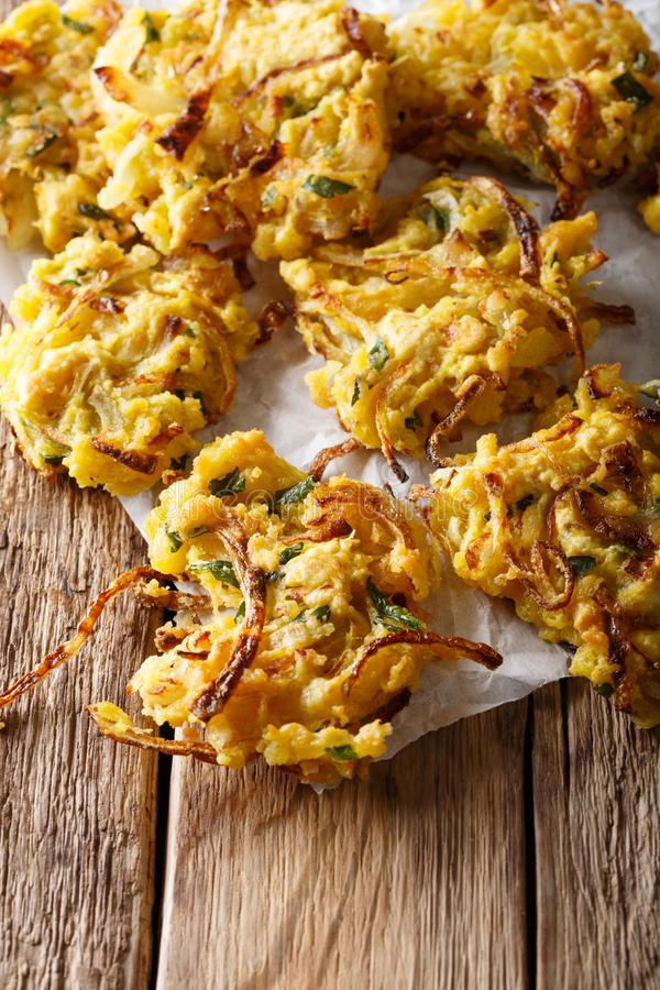 Crispy Onion Bhajis make the perfect naturally gluten free and v. Egan snack or starter closeup on tre table. vertical stock photo