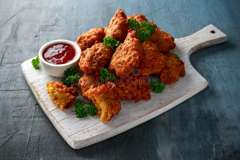 Crispy onion bhajis with sweet chilli sauce on white wooden board.  royalty free stock photos