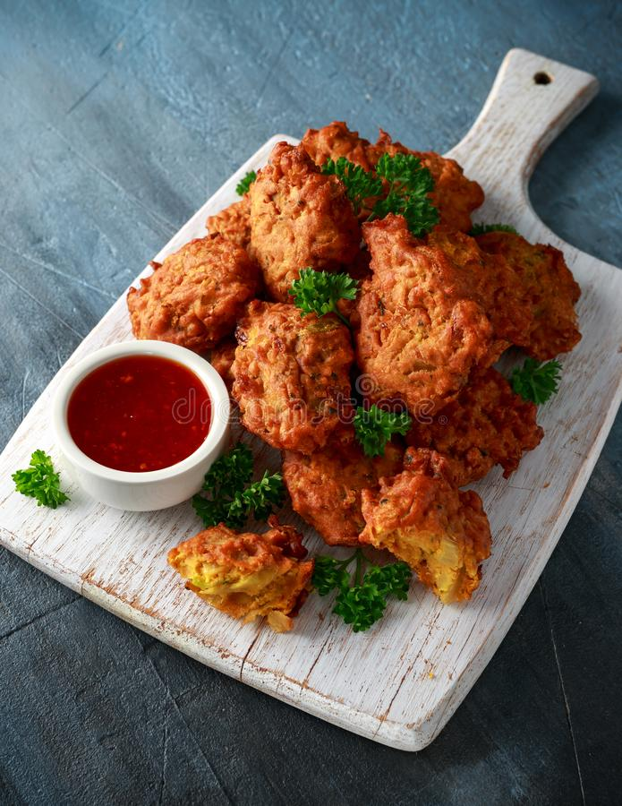 Crispy onion bhajis with sweet chilli sauce on white wooden board.  stock photography