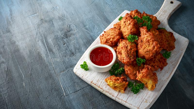 Crispy onion bhajis with sweet chilli sauce on white wooden board.  royalty free stock photography