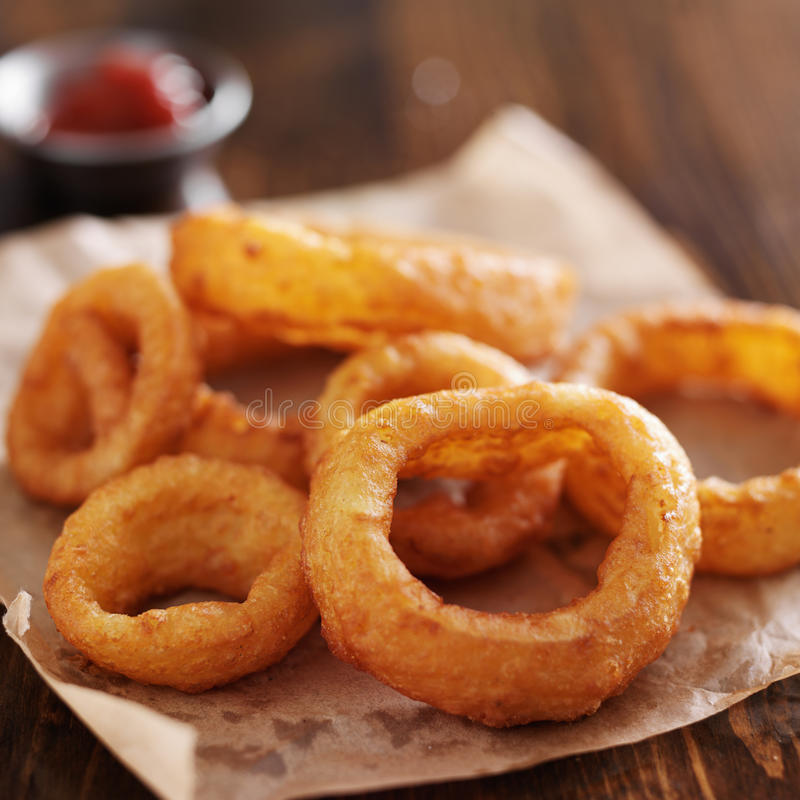Crispy onion rings. With ketchup on parchment paper stock photography