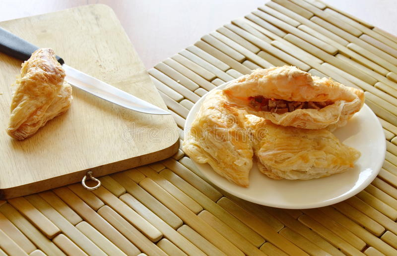Crispy pie filled pork sausage and crushed bean with wooden chop block. Crispy pie filled pork sausage and crushed bean on dish with wooden chop block stock photo