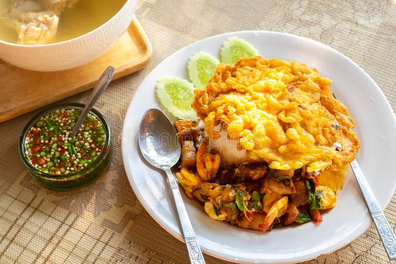 Crispy Pork Belly and Shrimp with Thai Basil on rice with Thai Style Omelet on Top royalty free stock photography
