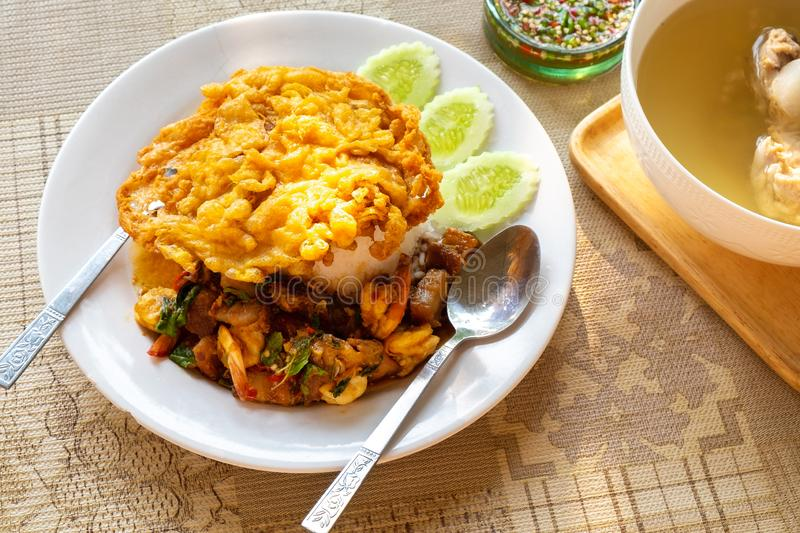Crispy Pork Belly and Shrimp with Thai Basil on rice with Thai Style Omelet on Top. stock image