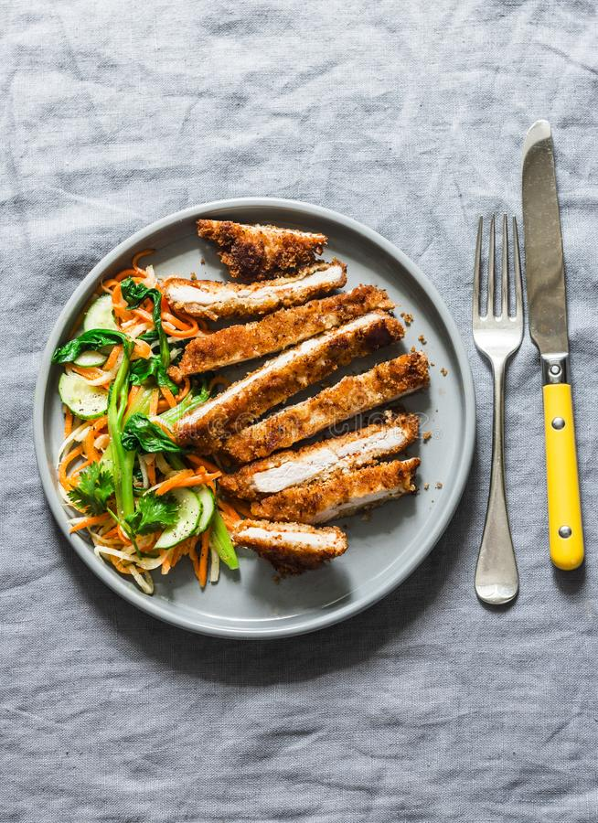 Crispy pork cutlet and quick pickled vegetables asian salad on grey background, top view.  stock images