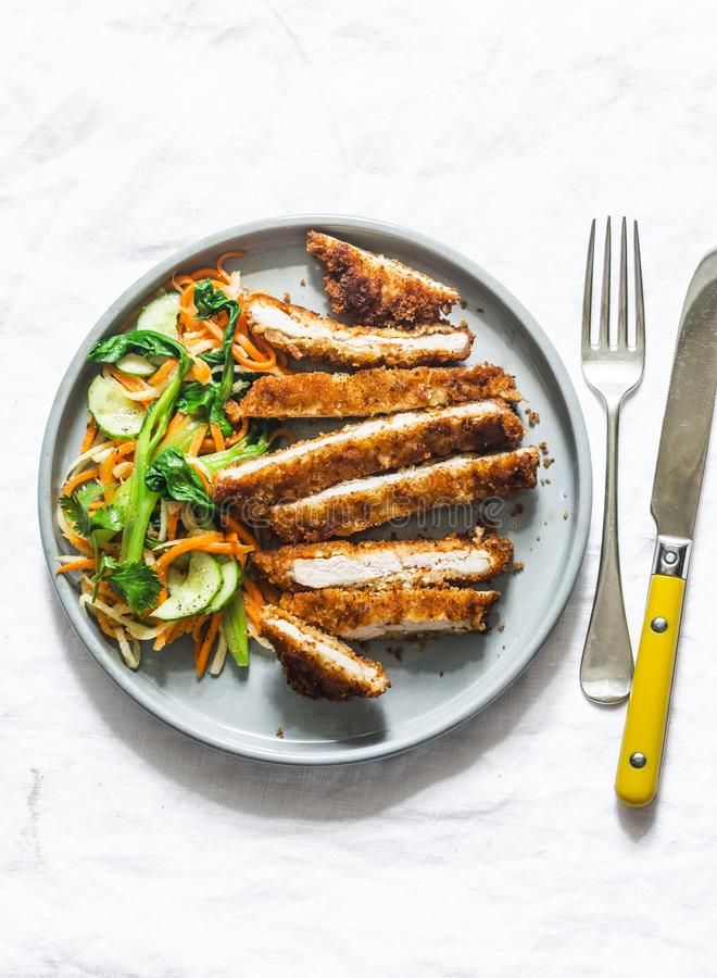 Crispy pork cutlet and quick pickled vegetables asian salad on light background, top view. Crispy pork cutlet and quick pickled vegetables asian salad on light stock photo