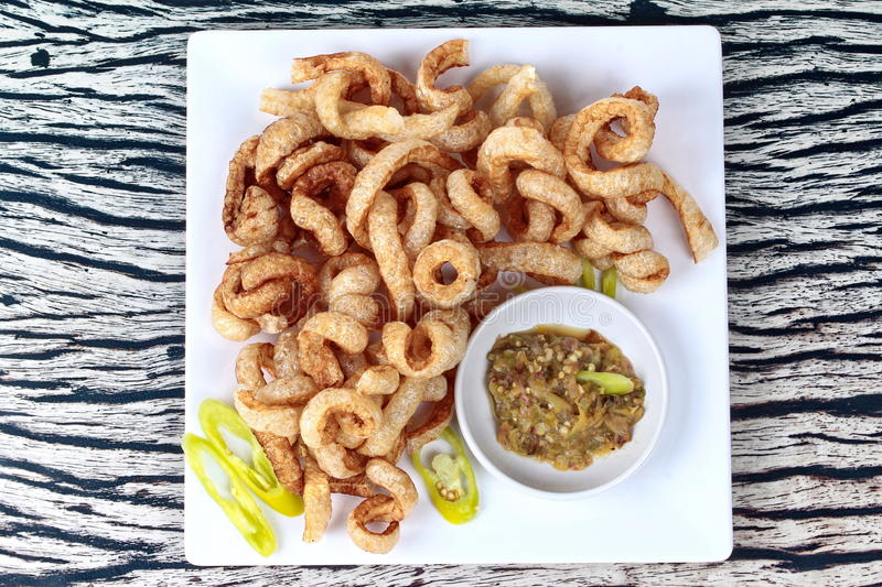 Crispy pork rind served with green chili dip . Thai food , Crispy pork rind served with green chili dip stock images