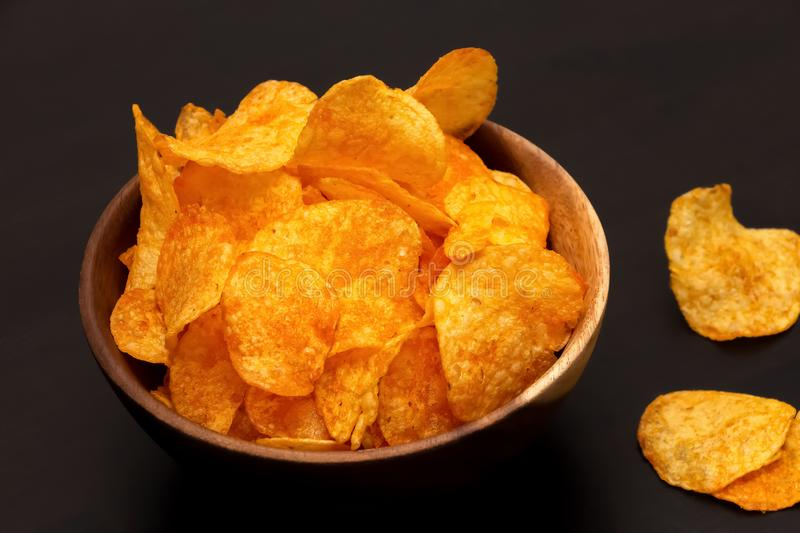 Crispy potato chips with paprika wooden bowl. Unhealthy vegan fast food. Top view. Copy space stock photography