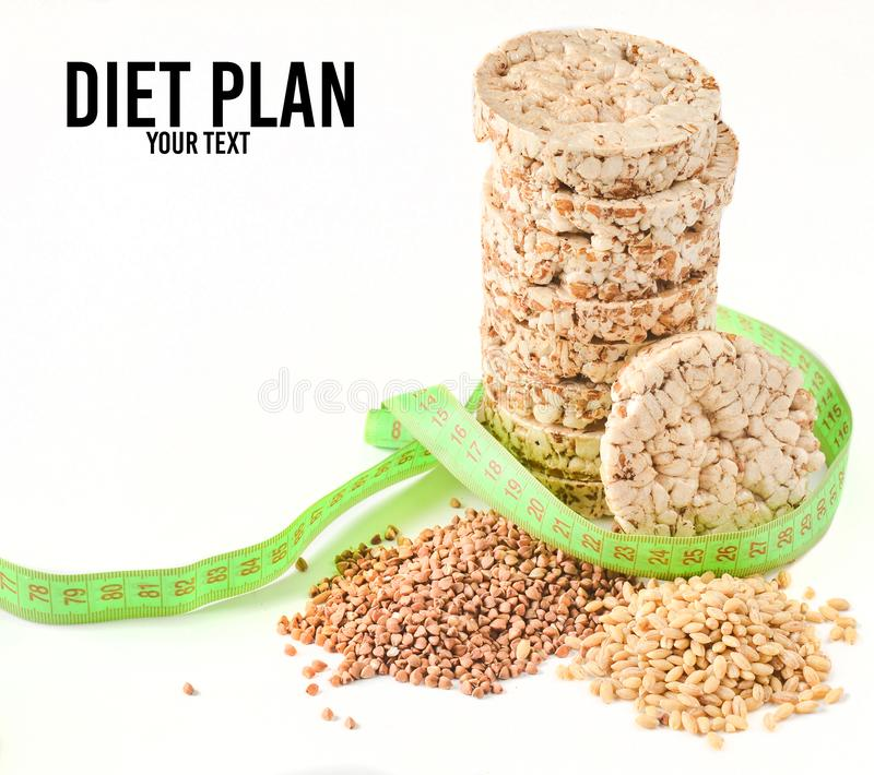 Crispy round dietary buckwheat rice fitness bread wrapped with a ruler isolated on white background.Eating for slimming. Crispy round dietary buckwheat rice royalty free stock photos