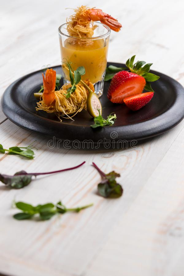 Crispy Shrimp in Kataifi Crust and Thyme with Champagne Sauce in glasses and strawberries lie on a black plate on a white woody royalty free stock photo