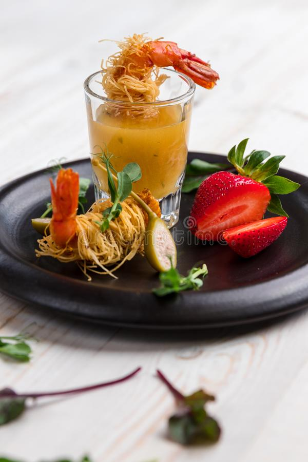 Crispy Shrimp in Kataifi Crust and Thyme with Champagne Sauce in glasses and strawberries lie on a black plate on a white woody stock photos