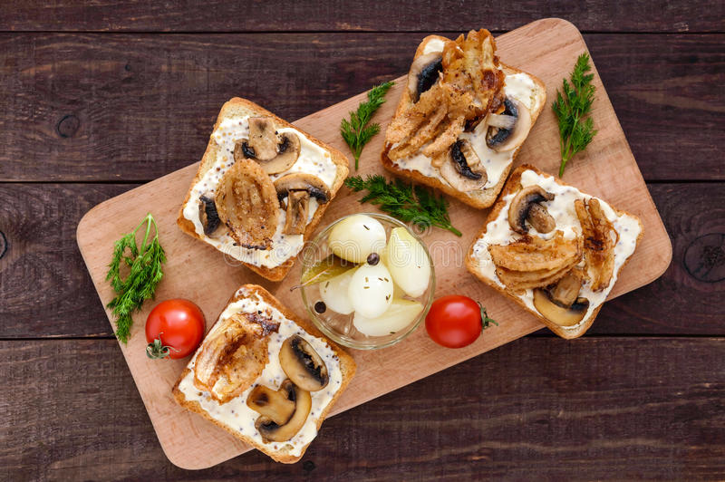 Crispy toasted white bread in the shape of a square with mushrooms, onions, french fries, tartar sauce. On a cutting board on a dark wooden background. The top stock photo
