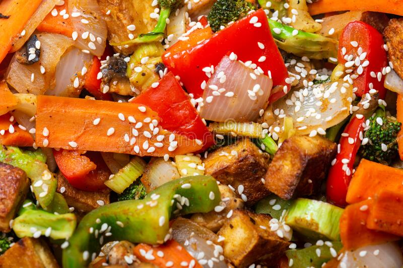 Crispy tofu with stir fried vegetables and sesame seeds royalty free stock photo
