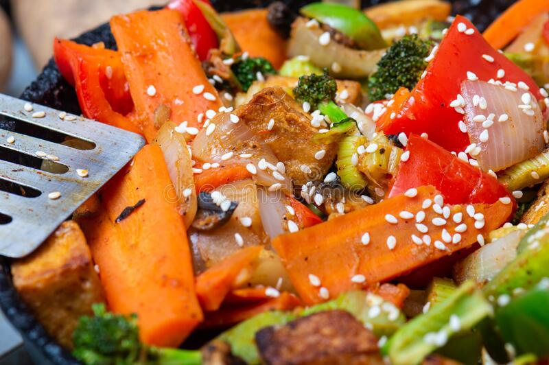 Crispy tofu with stir fried vegetables and sesame seeds royalty free stock photography