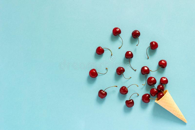 Crispy waffle ice cream cone with scattered red ripe sweet cherries. Still life on blue background. Copy space, Flat lay, Top view stock photography