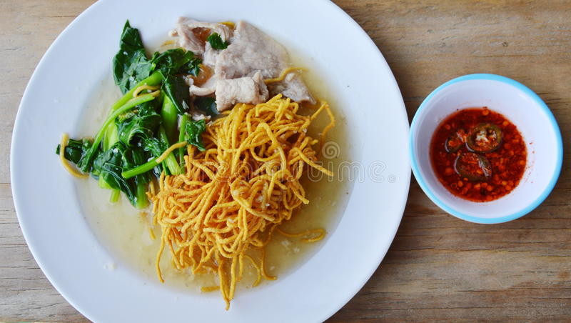 Crispy yellow noodle with Chinese kale and pork in gravy sauce. And chili sauce stock photo