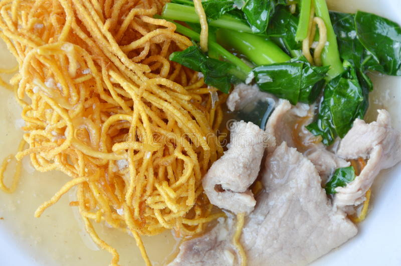 Crispy yellow noodle with Chinese kale and pork in gravy sauce. On plate royalty free stock photo