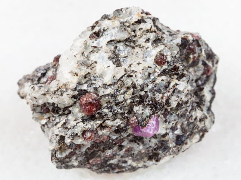 cristais ásperos do corindo na pedra do gneisse no branco imagem de stock royalty free