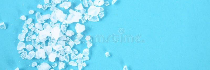Cristais do grandes sal e aneto do mar em uma tabela azul foto de stock