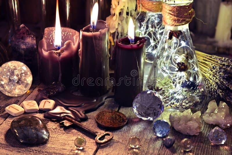 Cristais mágicos, objetos rituais, runas, velas pretas e garrafas na tabela da bruxa fotografia de stock royalty free