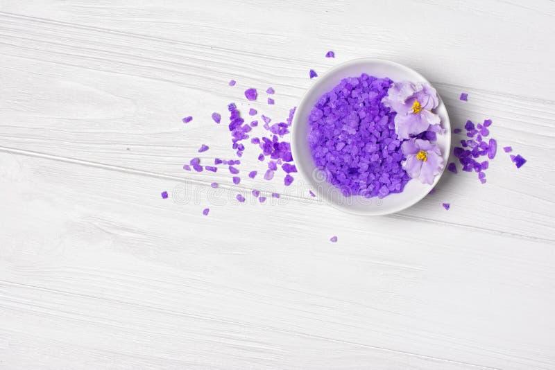 Cristais roxos Flavored de sal do mar para o banho com a flor violeta no branco imagens de stock