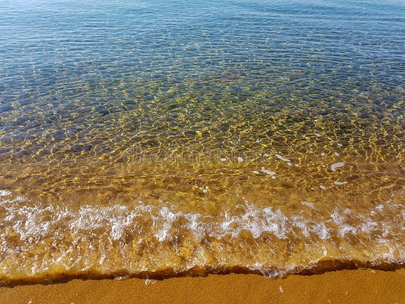 Cristal clear waves and golden sand stock images