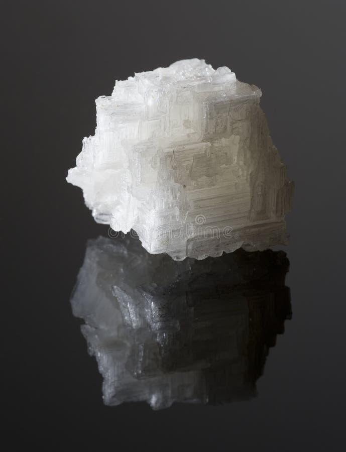 Cristal de sal do mar na superfície reflexiva preta fotografia de stock