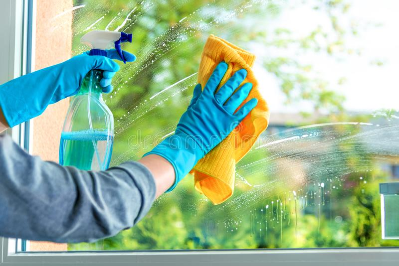 Cristal de ventana de la limpieza con el detergente fotografía de archivo