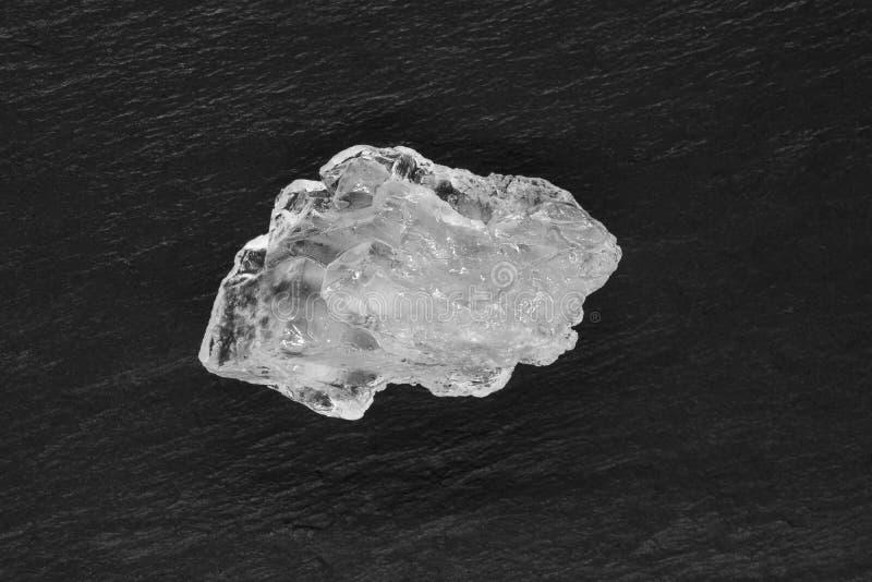 Cristal do açúcar ou do sal colocado na superfície de pedra preta do fundo foto de stock royalty free