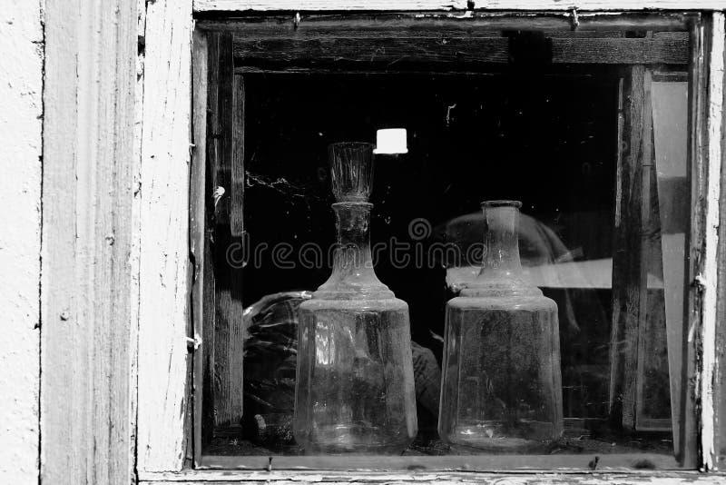 Cristalería de dos cocinas en la ventana de una casa vieja del pueblo imagen de archivo libre de regalías