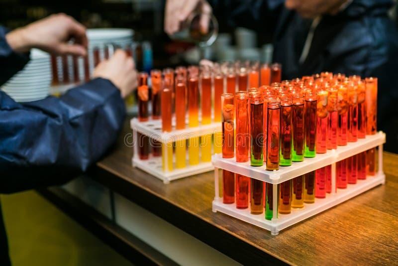 Cristalería de laboratorio con el cóctel del alcohol en partido químico foto de archivo