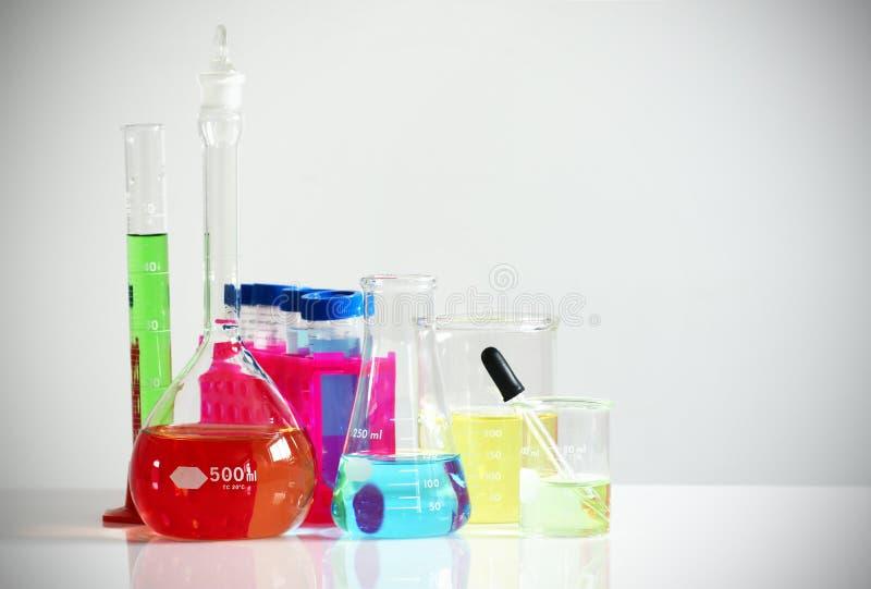 Cristalería de laboratorio con las sustancias químicas coloridas imagen de archivo