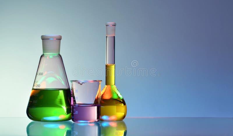 Cristalería de laboratorio con los líquidos coloridos en fondo azul imagen de archivo