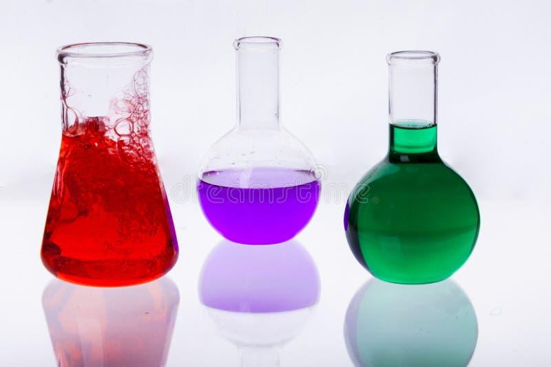 Cristalería de laboratorio con los líquidos de diversos colores en b blanco imagen de archivo libre de regalías