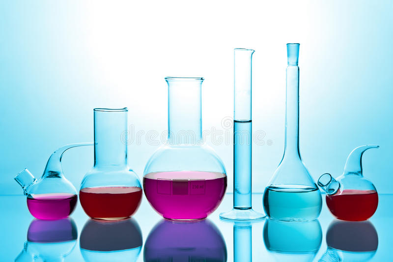 Cristalería de laboratorio con los productos químicos coloridos imagen de archivo